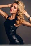 Beautiful sensual woman wtih blond curly hair in elegant black dress Stock Images