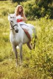 Beautiful sensual women riding on white horse Stock Photo