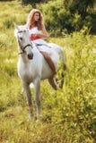 Beautiful sensual women riding on white horse Stock Photo