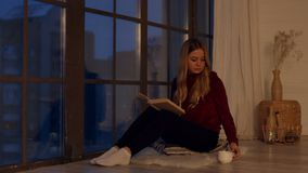 Pretty young woman reading book by window at home stock video