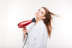 Beautiful sensual young woman in bathrobe drying hair with dryer Stock Photo