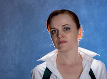 Beautiful sensual young woman in men`s shirt and tie on a blue background Royalty Free Stock Images