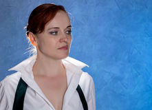Beautiful sensual young woman in men`s shirt and tie on a blue background Royalty Free Stock Image