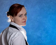 Beautiful sensual young woman in men`s shirt and tie on a blue background Stock Image