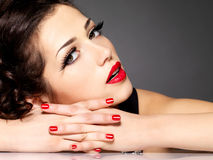 Beautiful sensuality woman with red nails and lips. Beautiful sensuality woman with red nails, lipstick and golden eye makeup  - on black background Stock Images