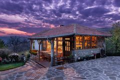 Traditional Serbian ethno house during a colorful sunset. Beautiful Serbian traditional ethno house at sunset with fluffy blue clouds on the sky and lights royalty free stock images