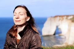 Woman smiling doing breath exercises on top of normandy cliffs in the spring. Beautiful serene Caucasian female model relaxing doing breath exercises and smiling stock photography