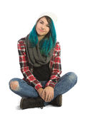 Beautiful serene girl sitting cross-legged. And looking straight at camera. Pierced, turquoise haired and dressing up a plaid jacket and blue jeans Royalty Free Stock Images