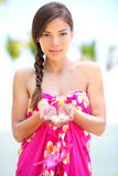 Beautiful serene woman on beach in sarong. Holding flower in palm of hands. Portrait of pretty graceful mixed race asian young woman on travel vacation on Stock Photography