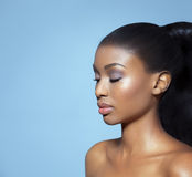 Beautiful Serene Woman. Portrait of beautiful serene African girl with closed eyes over blue studio background. African beauty with makeup and long hair Stock Photo