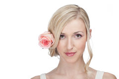 Beautiful serene woman with a rose in her hair Royalty Free Stock Photo