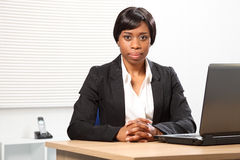 Beautiful serious african american business woman. Beautiful young African American woman working in office sitting to her desk with a serious, stern expression Stock Photography