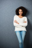 Beautiful serious African American woman. Leaning against a dark background with crossed legs and folded arms looking at the camera with copyspace and Stock Images