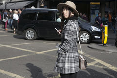 Beautiful serious Asian girl in a beige hat and a plaid coat cro Royalty Free Stock Photo