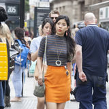 Beautiful serious Asian girl in a grey shirt and orange skirt crosses the road near Leicester Square Royalty Free Stock Image