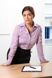 Beautiful serious business woman standing behind o Royalty Free Stock Photography