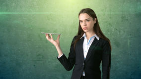 Beautiful serious businesswoman is holding the tray and looking at something Royalty Free Stock Image