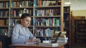 Beautiful serious caucasian female student sitting at table with books in library writing down summary in copybook using. Beautiful female student sitting at stock video