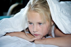 Beautiful serious girl looks out from under a blanket Stock Photography