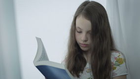 Beautiful serious little girl reading a book by window. stock video