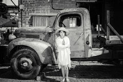 Beautiful serious little girl standing in front of old classic vintage retro truck Stock Photos