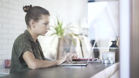 Beautiful serious office worker is typing at laptop stock footage