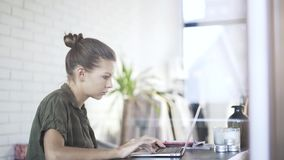 Beautiful serious office worker is typing at laptop, tilt down stock video