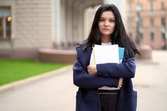 Free Beautiful Serious Smart Girl Brunette Student Holding Notebooks And Textbooks, Stands At University On Street Of St. Petersburg. A Stock Photo - 160722340