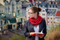 Beautiful serious woman in jacket and glasses reads red book against summer buildings Royalty Free Stock Photography