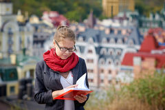 Beautiful serious woman in jacket and glasses reads red book against summer buildings Stock Images
