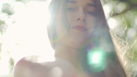 Beautiful serious woman low angle in bright light haze sun flare female portrait. Stock footage stock video