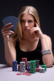 Beautiful serious woman playing poker in casino Royalty Free Stock Image