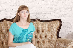 Beautiful serious woman sits on couch Stock Photos