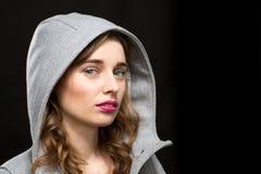 Beautiful serious woman wearing a grey hood Royalty Free Stock Photo