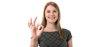 Beautiful serious young businesswoman in grey dress showing OK with her hand. Isolated white background stock footage