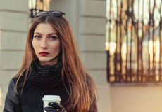 Beautiful serious young woman with coffee on the street Royalty Free Stock Photography