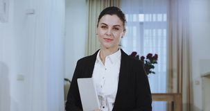 Beautiful and seriously real estate agent womna looking in front of the camera smiling large and holding a map then she. Go stock video footage