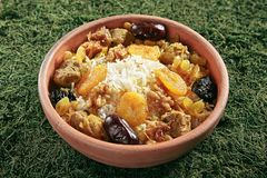 Beautiful Serving Vintage Ceramic Bowl of Turshu with Rice, Lamb Meat. Walnuts, Dried Fruits and Fragrant Saffron on Natural Moss and Wood. Homemade Mutton stock photo