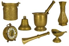 Beautiful set or collection of vintage brass or golden decorative house items isolated on white: clock, pestle, mortar, bell. Candle holder, chalice stock photo