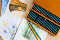 Beautiful set of watercolor paintings and luxury box of aquarelle pensils stock images