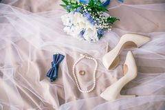 Beautiful set of women`s and groom`s wedding accessories. Bride`s morning. Bride`s bouquet of white tulips and blue flowers. The white shoes, pearl necklace Royalty Free Stock Photo