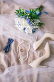Beautiful set of women`s and groom`s wedding accessories. Bride`s morning. Bride`s bouquet of white tulips and blue flowers. The white shoes, pearl necklace Stock Photos