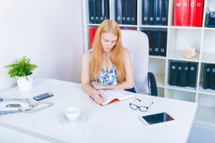 Beautiful young businesswoman sitting by wooden desk with notepad. Modern office worker in white room interior. Succesfull woman, Stock Photography