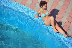 Beautiful sexual woman sitting near pool on resort Royalty Free Stock Images