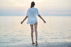 Beautiful sexual woman in white shirt and bikini walking on the beach against the sea and sunset. Happy woman enjoying summer vacation Royalty Free Stock Images
