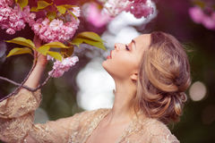 Beautiful sexy adult girl standing at blossoming tree in the garden Royalty Free Stock Images