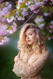Beautiful sexy adult girl standing at blossoming tree in the garden Royalty Free Stock Image