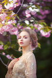 Beautiful sexy adult girl standing at blossoming tree in the garden Royalty Free Stock Photo