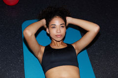 Beautiful sexy African-American woman swings press on the mat for yoga Royalty Free Stock Images
