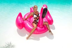 Beautiful sexy, amazing young woman in a swimming pool sitting on an inflatable pink flaming and laughing, tanned body, long hair stock photo
